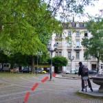 Am Brunnen vorbei sehen wir schon den Eingang des Gewerbehofs am anderen Ende des Platzes.