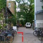 Nach den Fahrradständern befindet sich links eine weiße Tür.